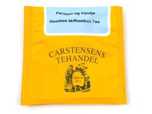 Tebrev med Fersken og Vanille te til undervejs eller bare til en enkelt god kop te. Grøn Rooibos urte te fra Sydafrika. Teblanding med kandiserede papayastykker, ferskenstykker, vanillestykker, solsikkeblomster og rosenblade.