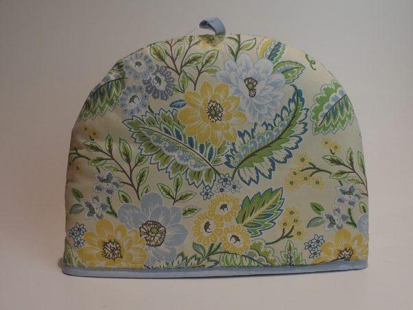 Tehætte med motiver af smukke hvide, gule og blå blomster.